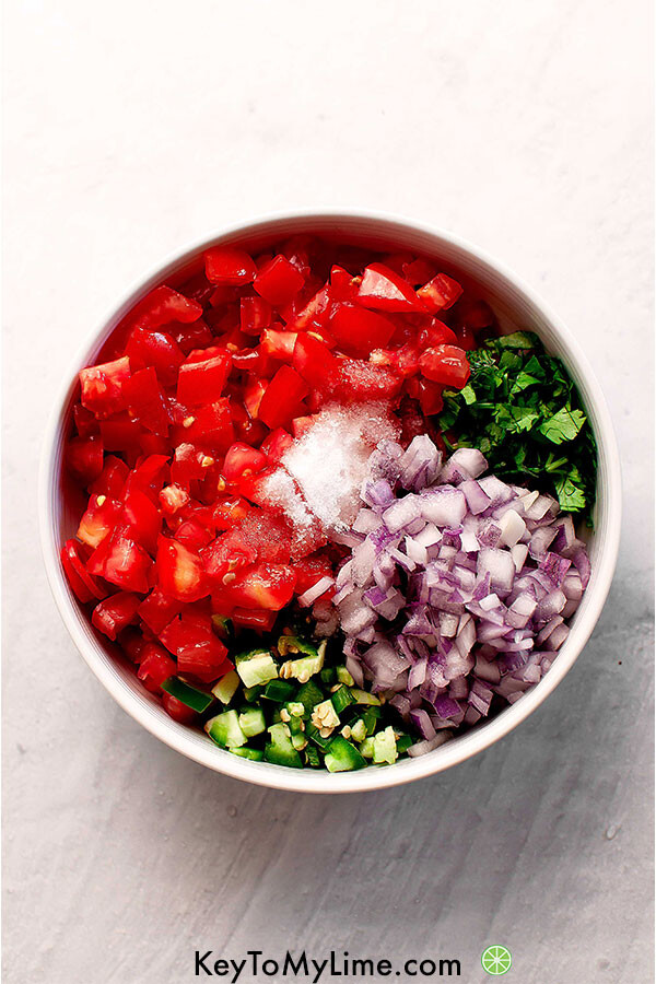 Cilantro, tomato, salt, sugar, jalapeno, lime, and red onion in a bowl.