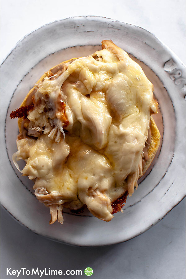Chicken with melted cheese on a bun.