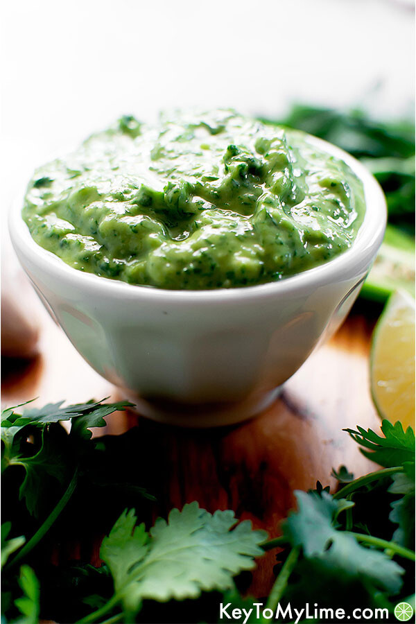 Creamy green sauce in a bowl surrounded by the ingredients.