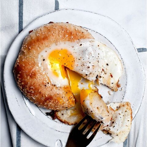 Egg in a hole bagel on a plate with runny yolk and a fork.