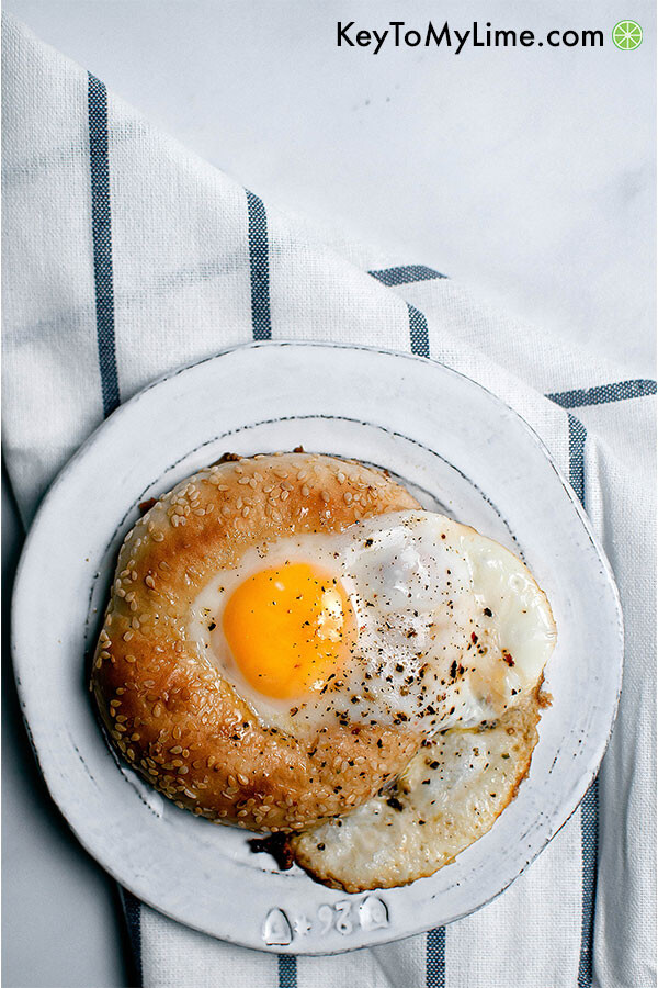 Egg in a hole bagel on a plate.