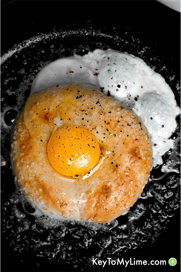 Half bagel in a skillet with a raw egg in the bagel hole.