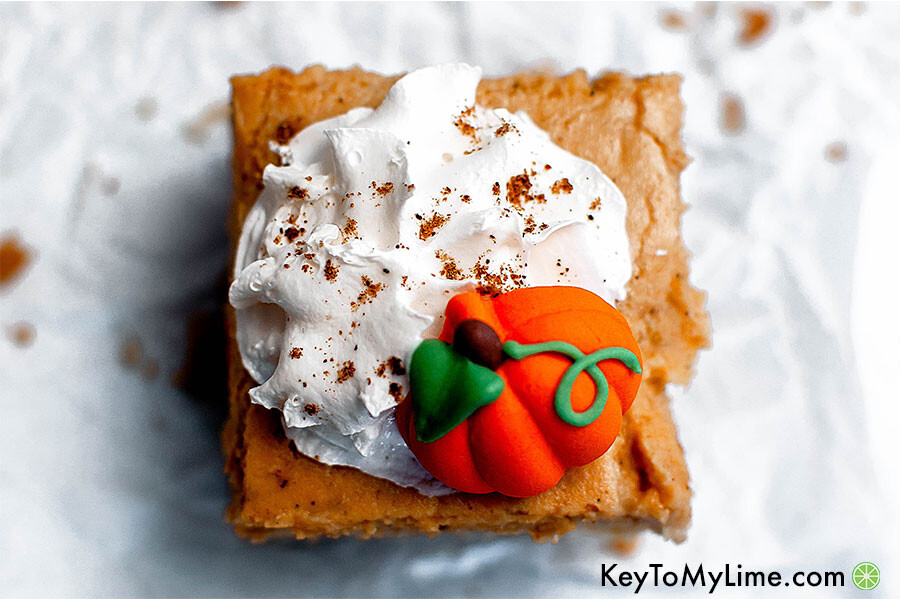A pumpkin pie cheesecake bar topped with whipped cream.