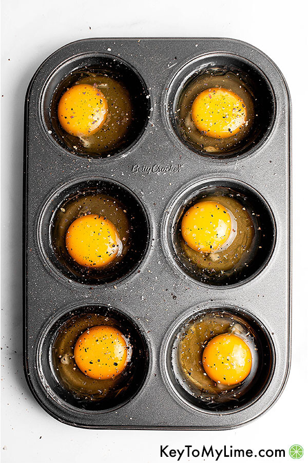 Raw eggs in a muffin pan.