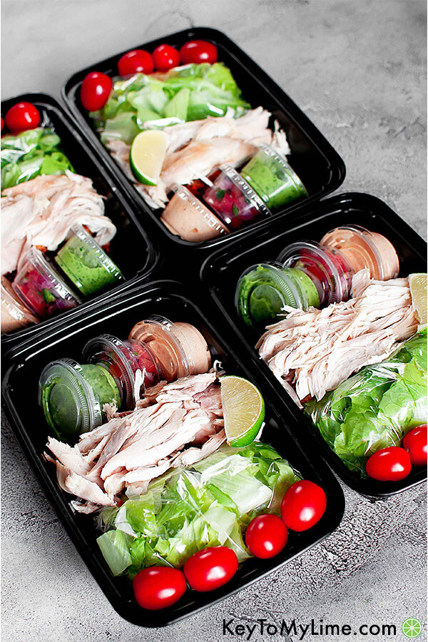 Meal prep containers with rotisserie chicken, lettuce, tomato, lime, and three sauces.