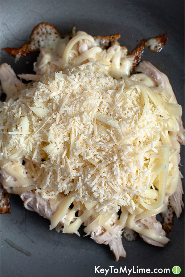 Chicken and cheese in a skillet.