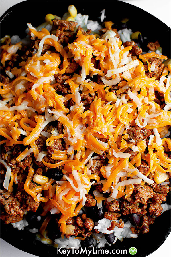 Sauteed onions, rice, black beans, corn, ground turkey taco meat, and shredded cheese in a skillet.