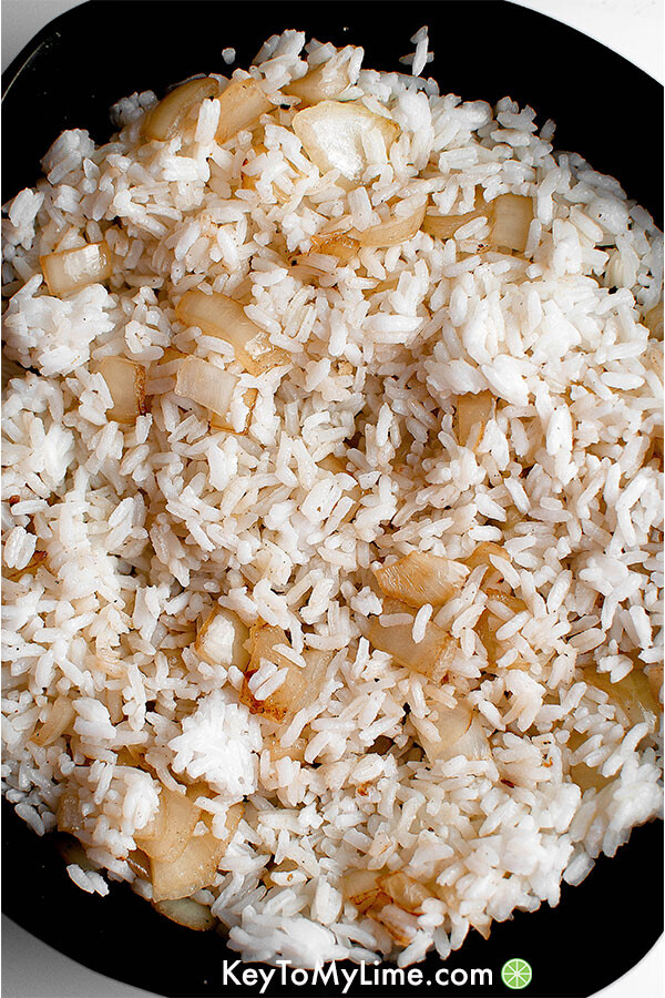 Sauteed onions and rice in a skillet.