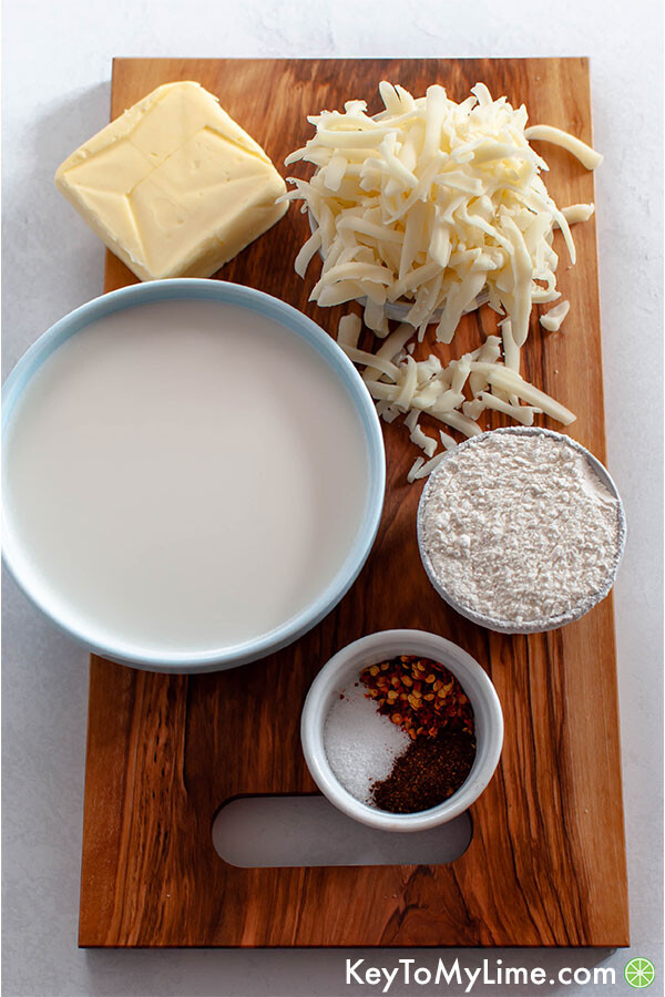 Milk, butter, flour, cheese, and spices on a cutting board.