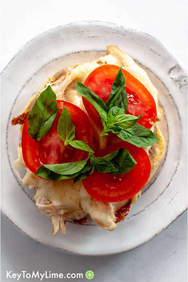 Tomato, basil, chicken, and cheese on a bun.