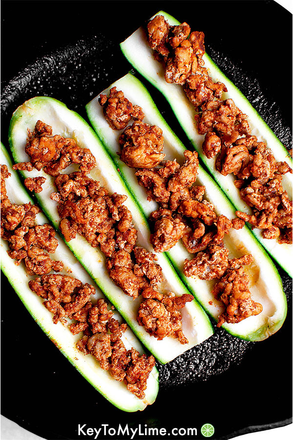 Zucchini boats being assembled in a skillet.