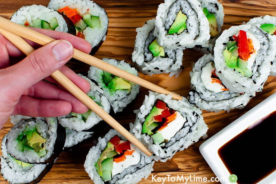 Vegan sushi filled with red bell pepper, carrot, cucumber, and avocado on a board.