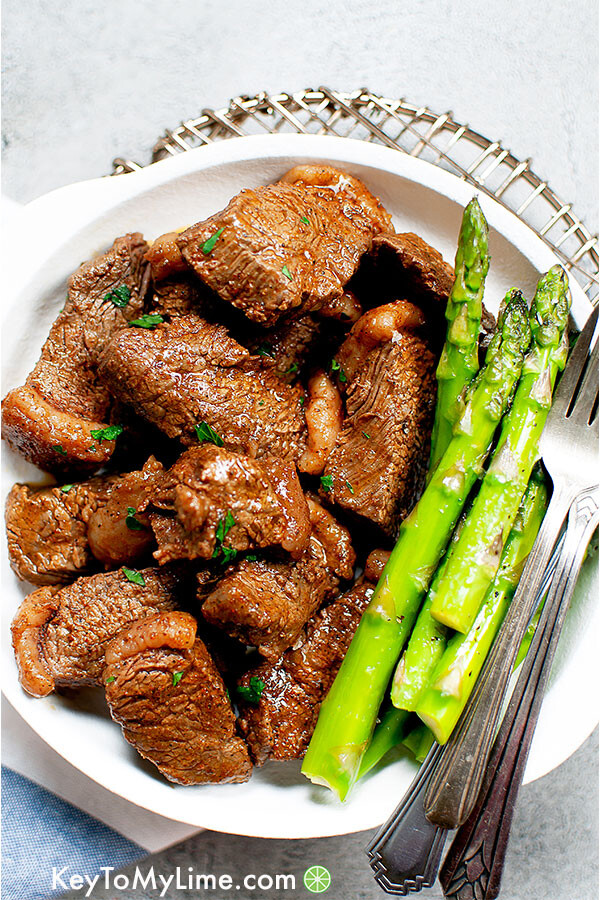 Cajun butter steak bites on a white plate with asparagus.