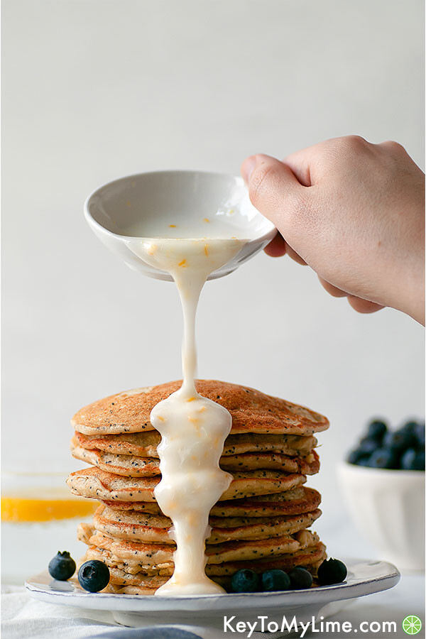 Lemon glaze being poured on a stack of gluten free pancakes.