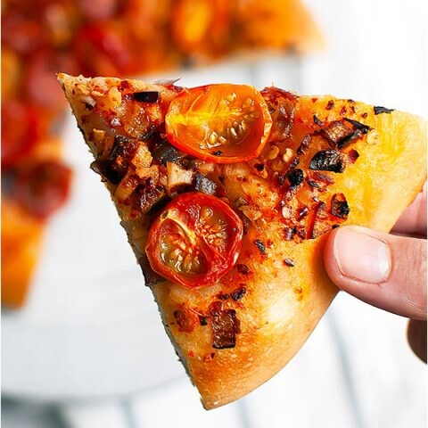 A hand holding a slice of vegan pizza.