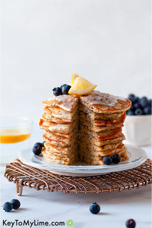 A stack of lemon poppy seed pancakes with a bite missing.