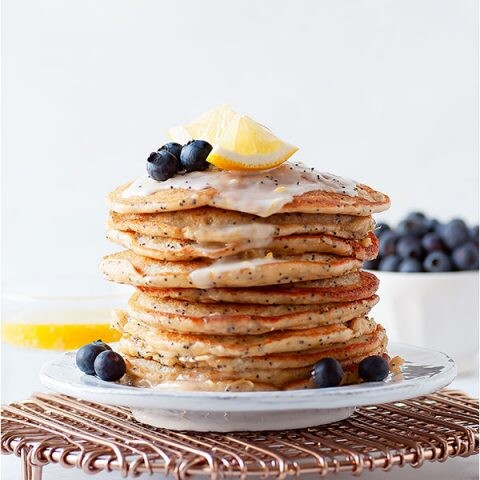 A stack of gluten free lemon poppy seed pancakes with blueberries as garnish.