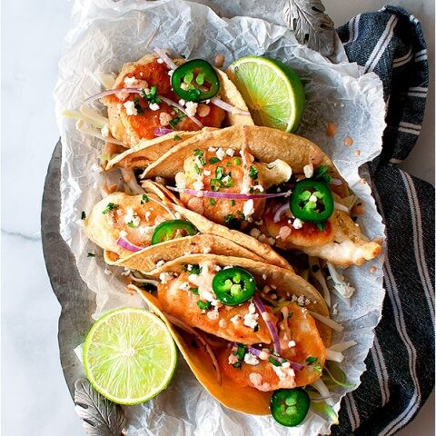 Beer battered chicken tacos on a silver tray with a navy napkin.