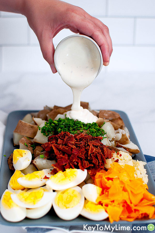 Hand pouring dressing onto loaded baked potato salad.