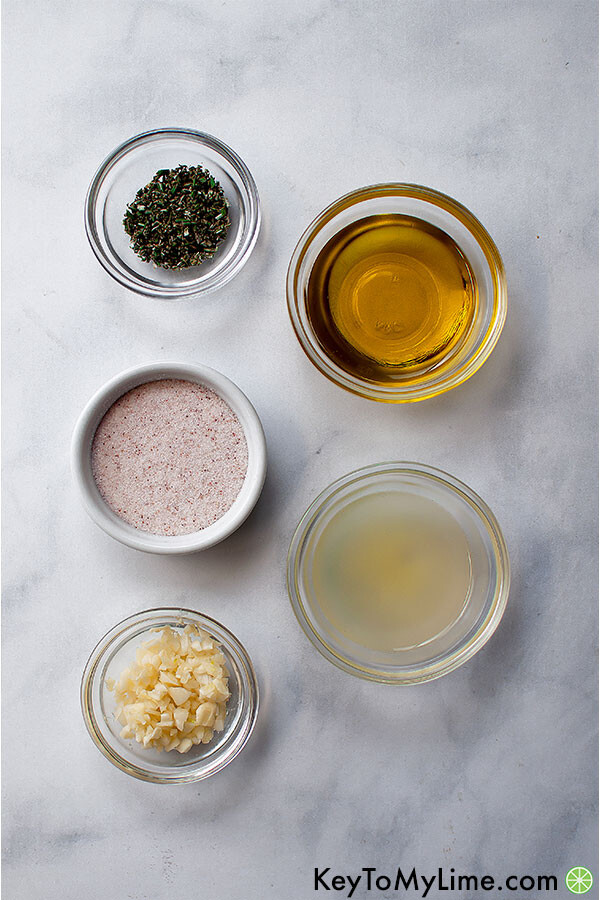 Lemon rosemary garlic marinade ingredients in small containers on a marble background.