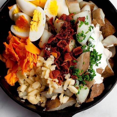 The ingredients for loaded baked potato salad displayed in a bowl.