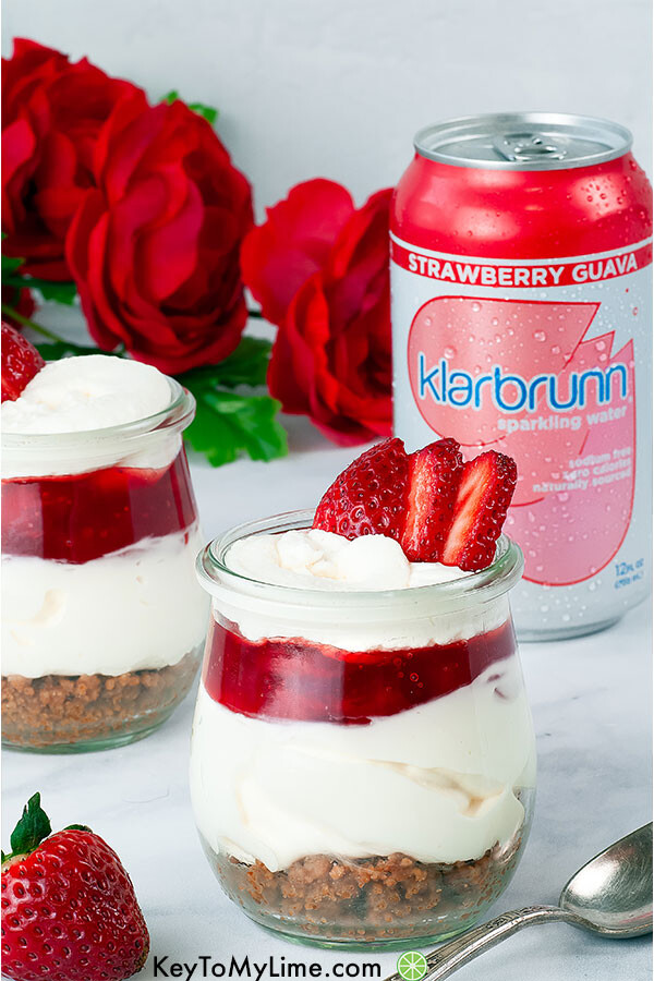 Two strawberry cheesecake cups with Klarbrunn water and Valentine's Day red roses.