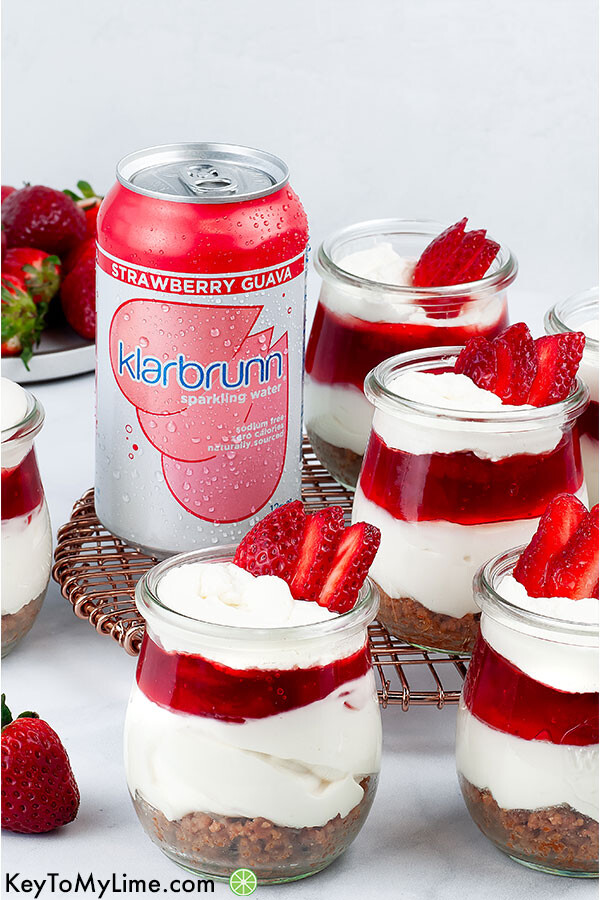Five strawberry cheesecake cups and a can of Klarbrunn Strawberry Guava Sparkling Water.