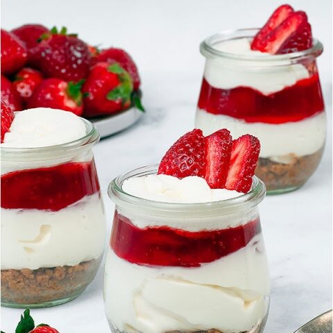 Three strawberry cheesecake cups on a white background.
