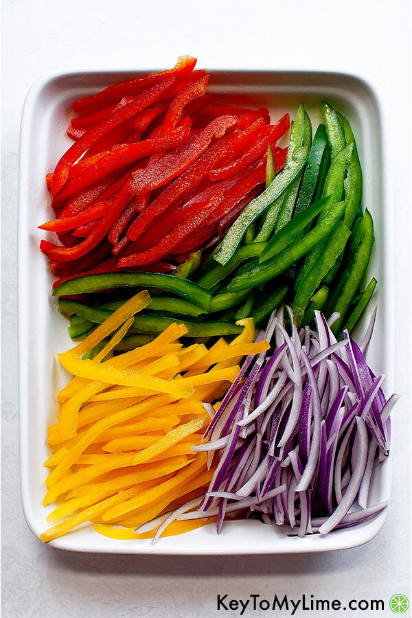 Red bell peppers, green bell peppers, yellow bell peppers, and red onions.