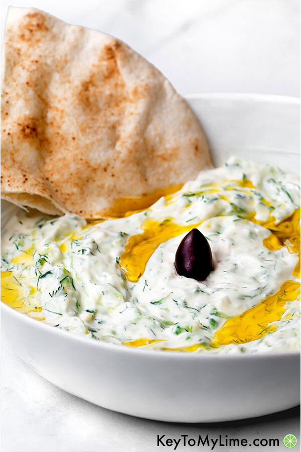 Easy tzatziki sauce in a white bowl with a piece of pita.
