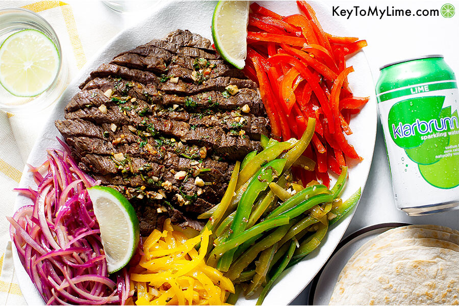 Sliced flank steak on a platter with bell peppers and onion.