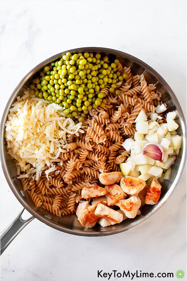 Pasta with peas ingredients in a silver skillet.