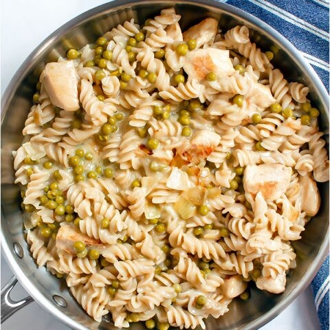 Pasta with chicken and peas in a silver skillet.
