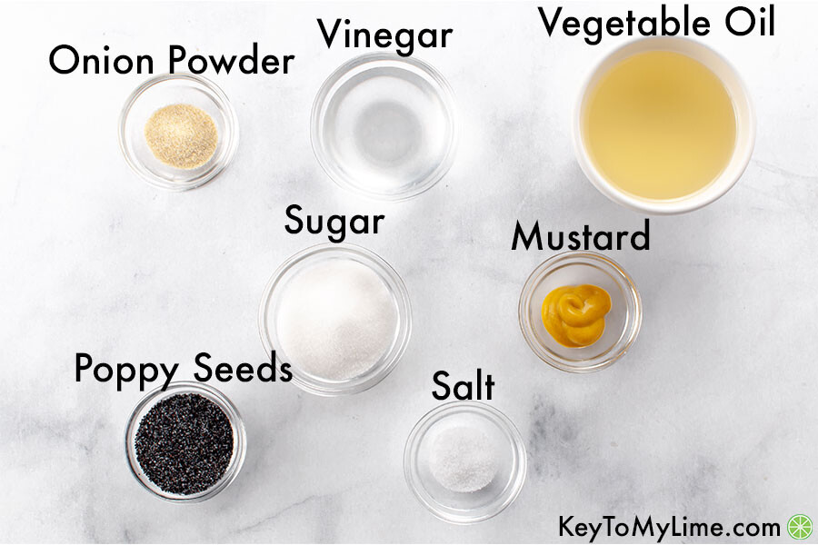 The ingredients for poppy seed laid out on a marble background and labeled.