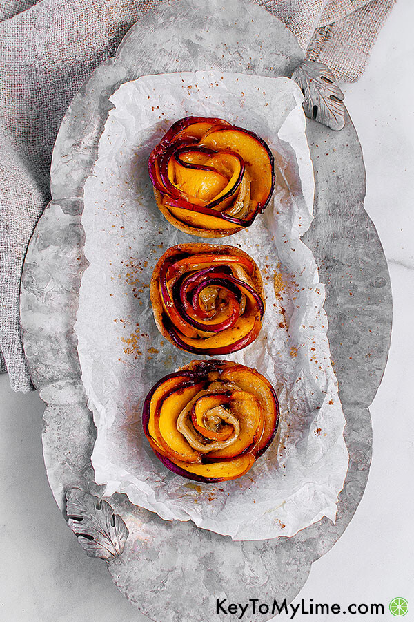 Three peach rose tarts on a silver tray with a linen napkin.