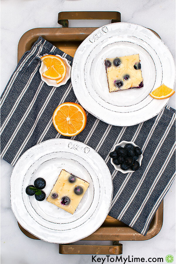 An overhead image of two lemon blueberry bars. Each bar is on a white plate on top of a striped dark blue cloth napkin.