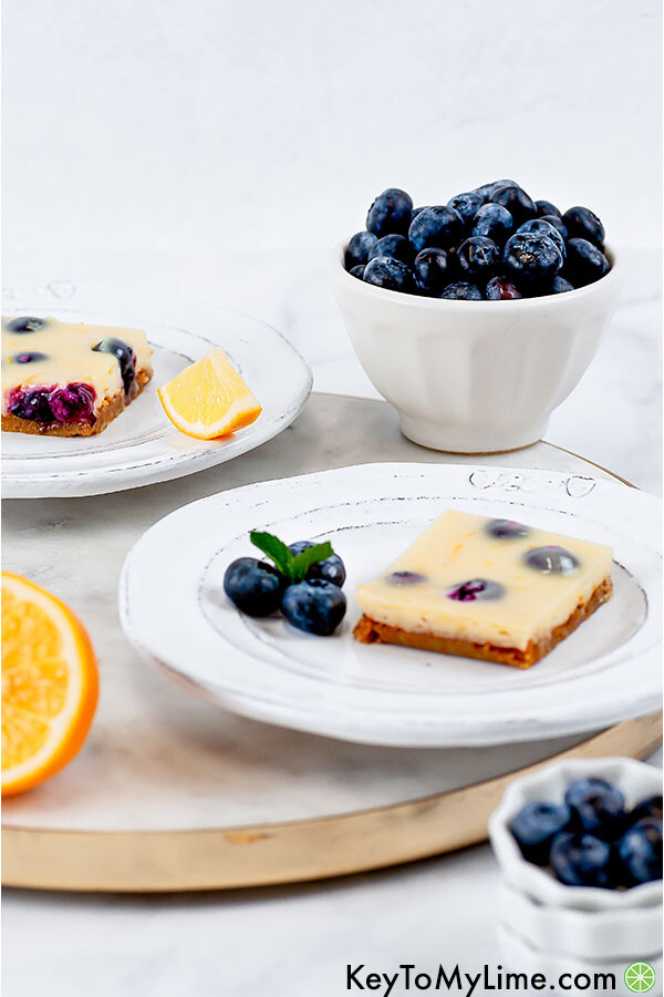 A side image of two lemon blueberry bars on white plates on top of a marble slab with a bowl of blueberries in the background.