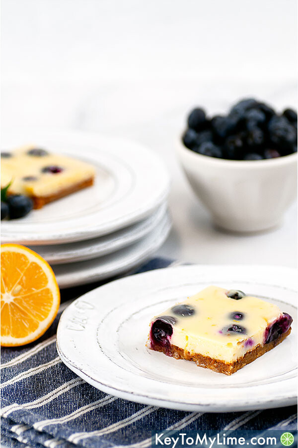 A side image of a lemon blueberry bar on top of a striped blue napkin with a pile of white plates and a bowl of blueberries in the background.