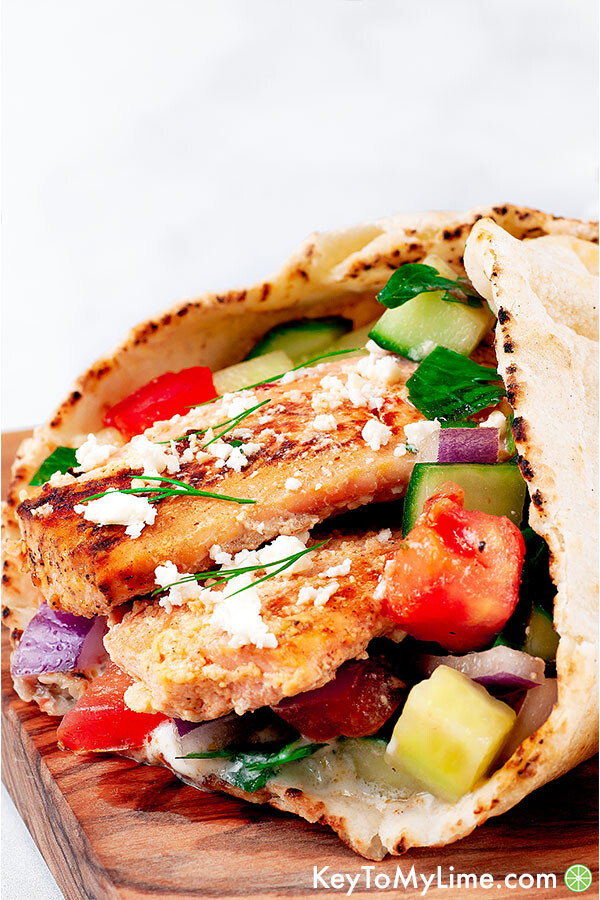 A close up side image of a salmon gyro on a wood board against a white background.