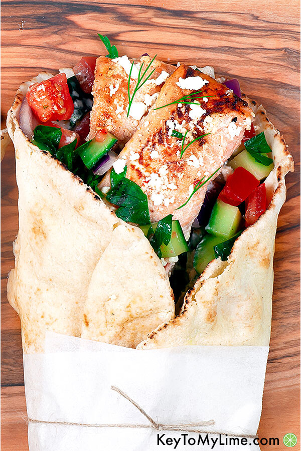 An overhead close up image of a salmon gyro on a wooden board.
