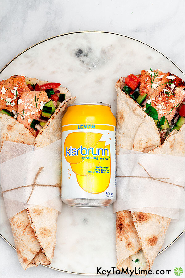 An image of two salmon gyros with a can of lemon sparkling water.