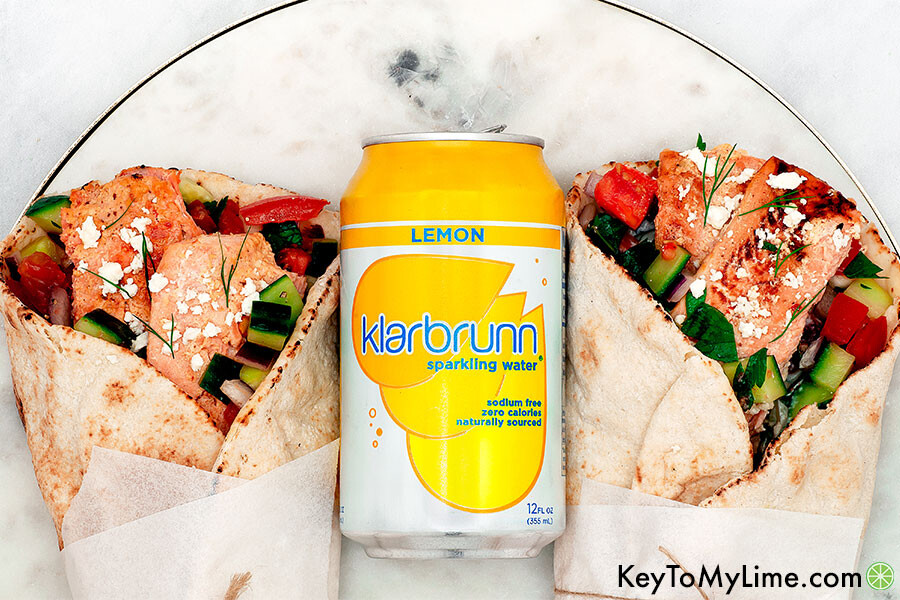 An overhead image of two gyros on a marble board with a can of lemon Klarbrunn sparkling water.