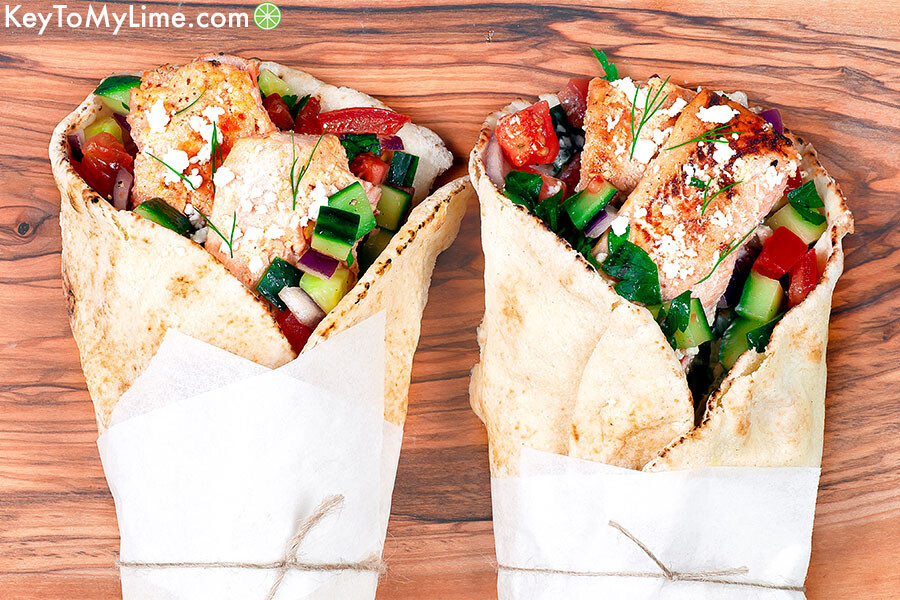 An overhead image of two salmon gyros on a wood cutting board wrapped in parchment paper.