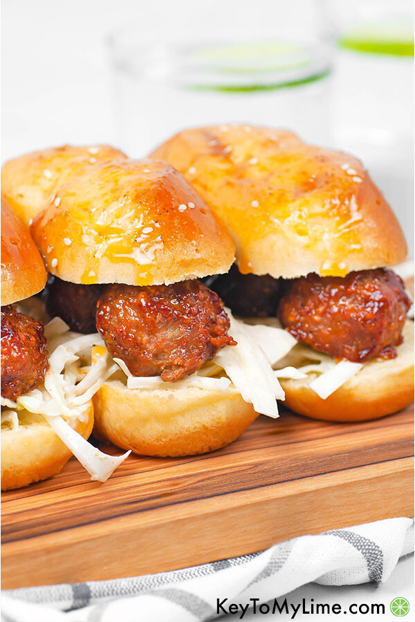 A wood board with three bbq meatball slider subs.