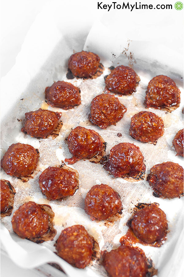 A parchment paper lined baking sheet with cooked bbq turkey meatballs.