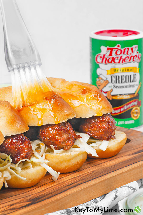 Cajun BBQ meatball sliders on a wood board with a brush basting melted cajun butter on top.