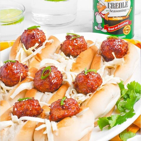 A side image of bbq meatball sliders on an oval platter.