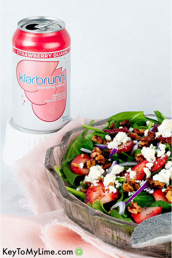 A side image of strawberry spinach salad in a glass bowl.