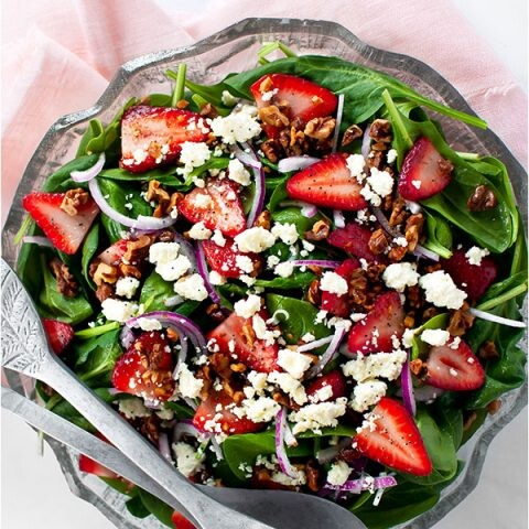 An overhead image of strawberry spinach salad in a glass bowl on a pink napkin.
