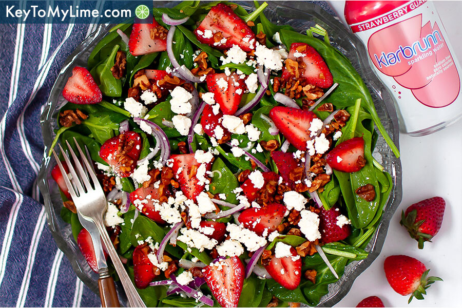 An overhead image of strawberry spinach salad with a fork and knife on a blue striped napkin.